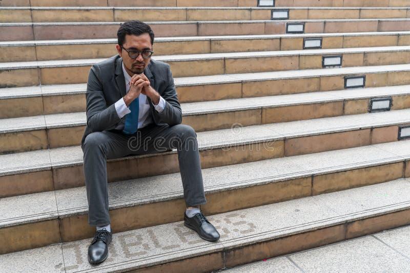 Ein trauriger schauender junger Geschäftsmann, der am Treppenhaus sitzt stockbilder