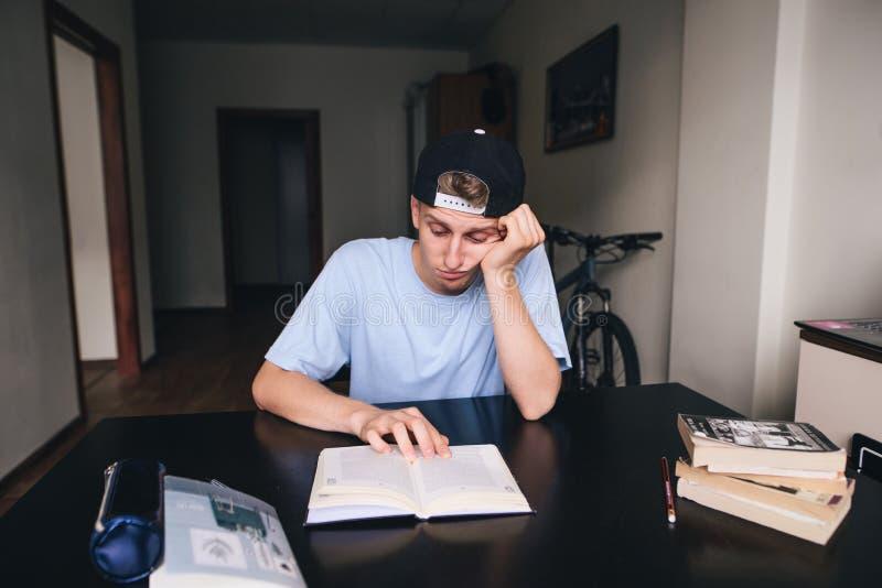 Ein trauriger Student ist widerstrebend, ein Buch in seinem Raum zu lesen Handeln von Heimarbeit Zu Hause unterrichten lizenzfreies stockfoto
