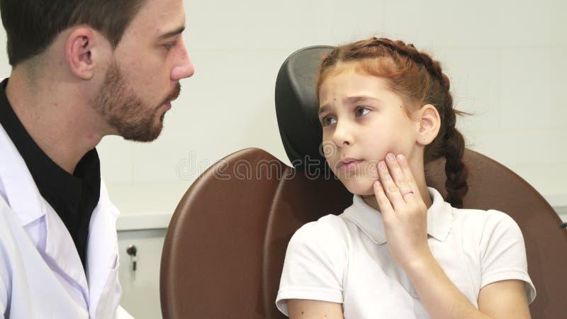 Ein trauriges Mädchen beschreibt ihre Zahnschmerzen zum Doktor stockfoto