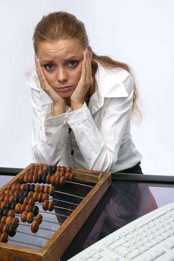 Ein trauriges Mädchen mit Tastatur und Rechnungen lizenzfreies stockbild