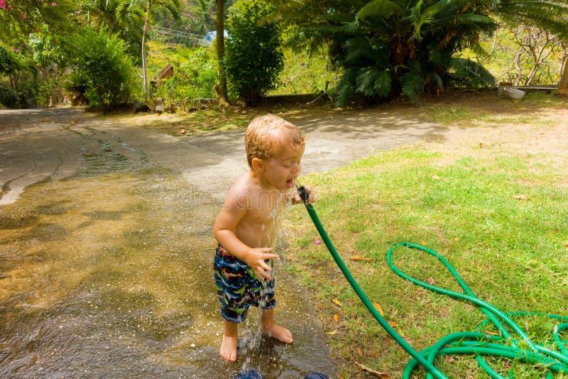 Ein Trinkwasser des Kleinkindes von einem Schlauch lizenzfreie stockbilder
