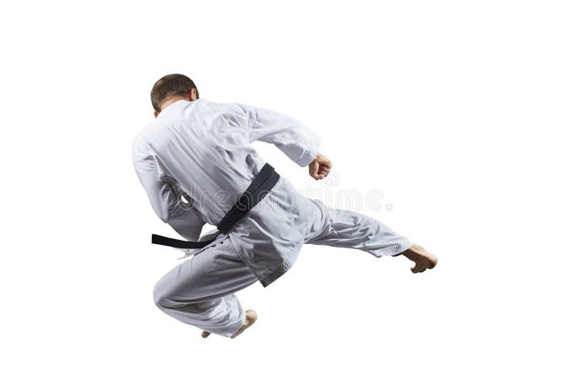 Ein Tritt im Sprung, den ein Athlet auf einem weißen lokalisierten Hintergrund ausbildet stockfotografie