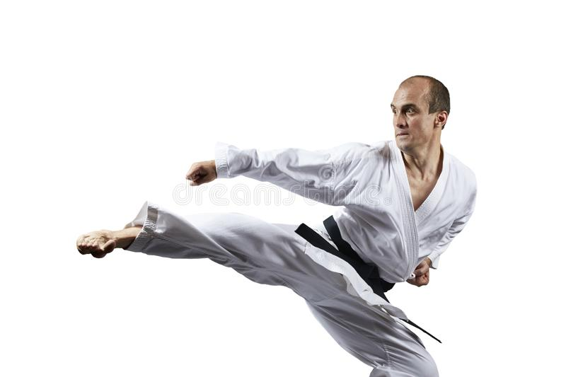 Ein Tritt schlug durch einen Athleten mit einem schwarzen Gürtel auf einem weißen lokalisierten Hintergrund stockbilder