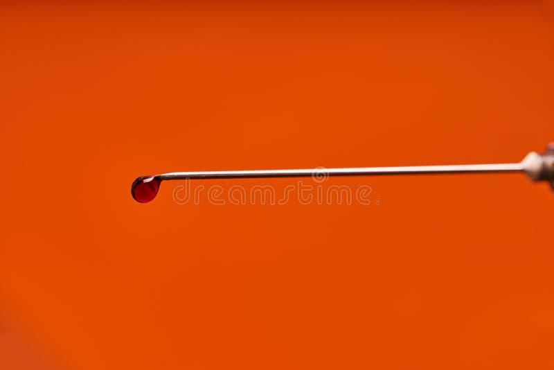 Ein Tropfen von Medizin auf der Spitze einer medizinischen D?sennadel Roter Hintergrund stockfotografie