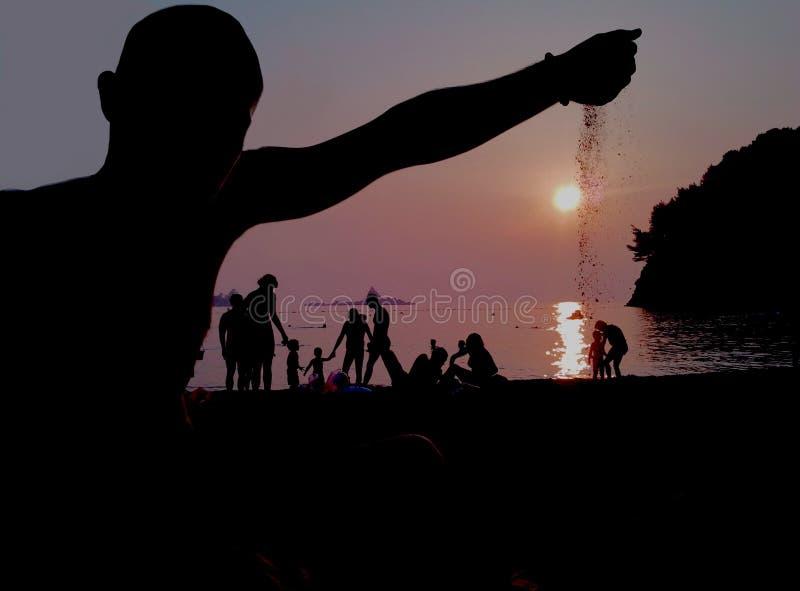 Ein troving Sand des Kerls im Sonnenuntergang auf einem sandigen Strand lizenzfreie stockfotografie
