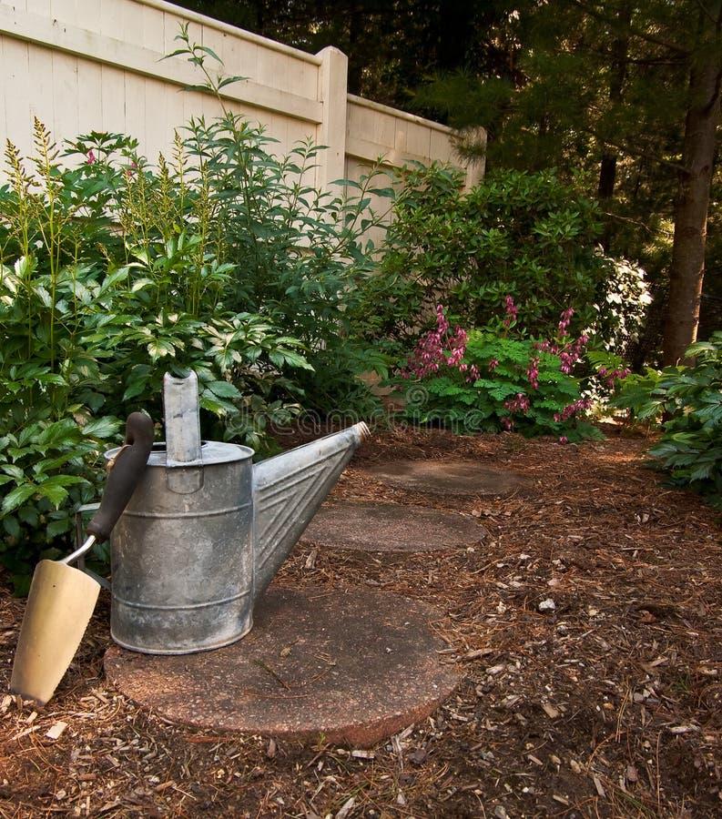Ein Trowel und alte eine Bewässerungs-Dose stockbilder