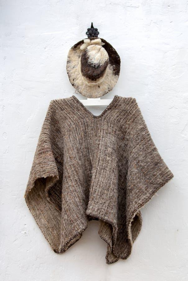 Ein typischer Hut und ein ruana, die von einer Wand hängen lizenzfreie stockfotografie