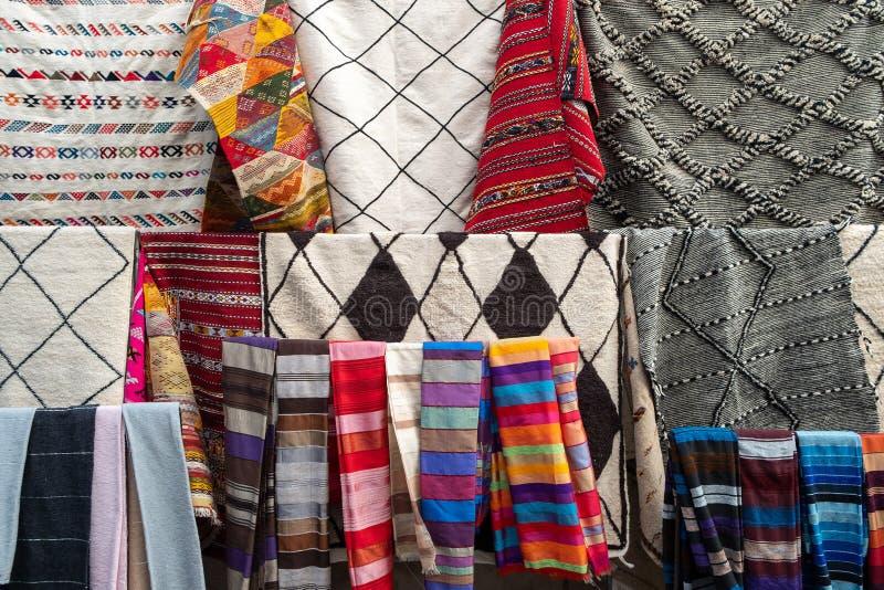 Ein typischer Marktstall, der eine Strecke der Kleidungs und der Trinkets an Touristen in Marrakesch verkauft stockfoto