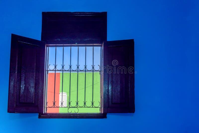 Ein typisches kubanisches Fenster, welches die Wand und den Himmel übersieht, ist blau, lizenzfreies stockfoto