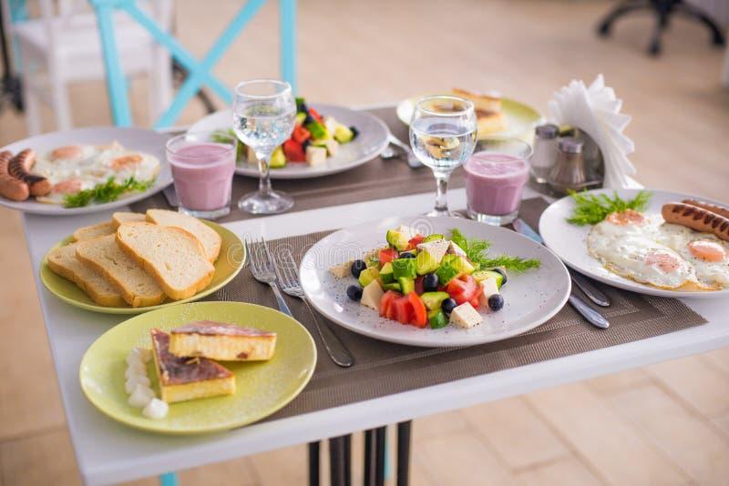 Ein umfassendes Frühstück von durcheinandergemischten Eiern mit Würsten, griechischem Salat und Käsekuchen lizenzfreies stockbild