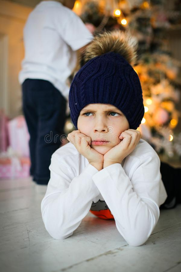 Ein umgekippter Junge nahe Tannenbaum im Silvesterabend stockbild