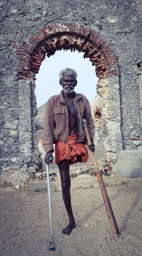 Ein Unbekanntes focht physikalisch Mannstellung vor einer verlassenen Kirche an stockbild
