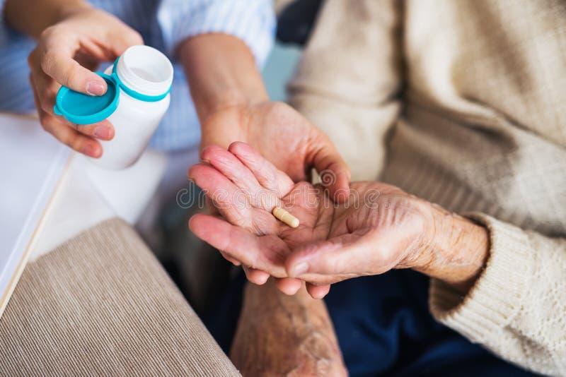 Ein unerkennbarer Gesundheitsbesucher, der eine ältere Frau im Rollstuhl erklärt, wie man Pillen nimmt lizenzfreie stockbilder