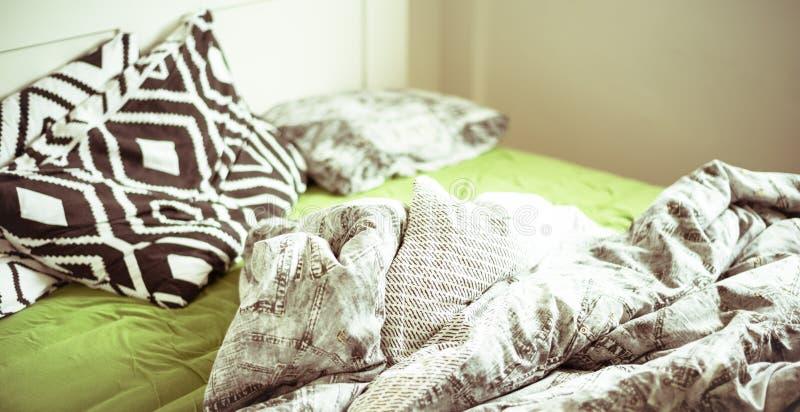Ein ungemachtes Bett mit Leinen und grünem Blatt stockfotografie