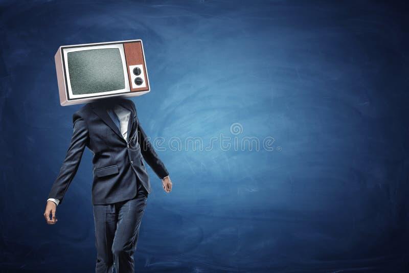 Ein unsicherer Geschäftsmann, der ungleich mit einem großen Retro- Fernsehen auf seinem Kopf zeigt graue Geräusche steht lizenzfreies stockfoto
