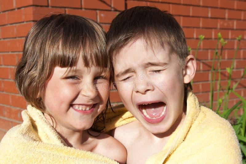 Ein unterhaltendes Mädchen und ein Junge werden in einem Tuch eingewickelt lizenzfreie stockbilder