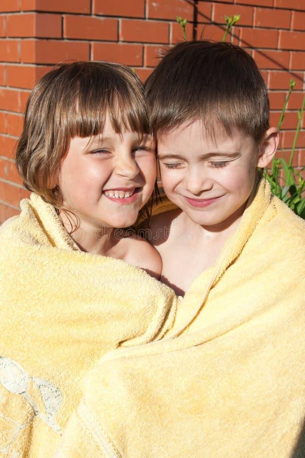 Ein unterhaltendes Mädchen und ein Junge werden in einem Tuch eingewickelt stockbild