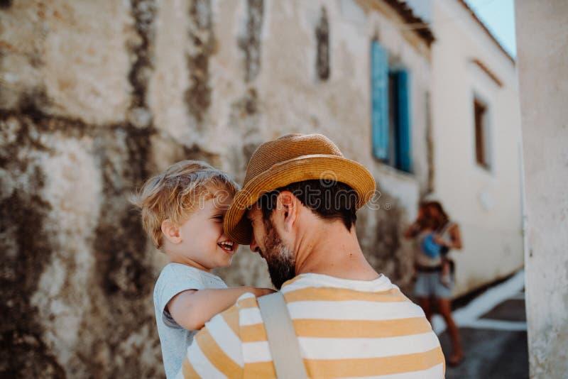Ein Vater, der einen Kleinkindsohn in der Stadt an den Sommerferien hält lizenzfreie stockfotos