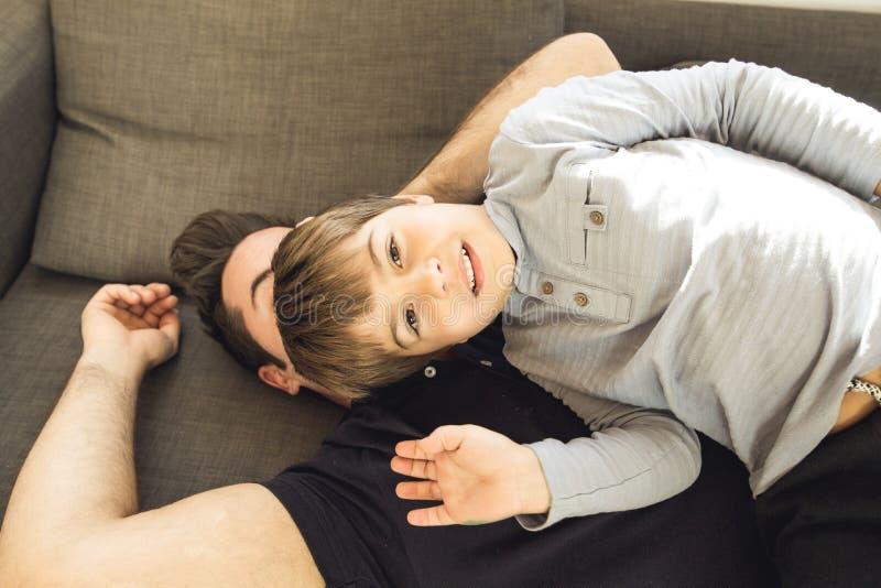 Ein Vater, der zu Hause auf der Couch mit seinem Sohn spielt stockbilder
