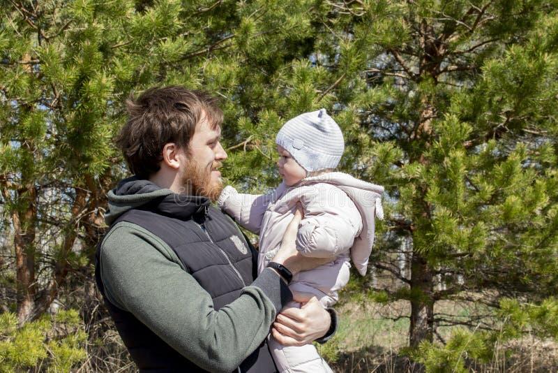 Ein Vater mit einem Baby in seinen Armen geht in den Park Ein junger Mann mit einem Bart h?lt ein Kinderm?dchen 9 Monate stockfotografie