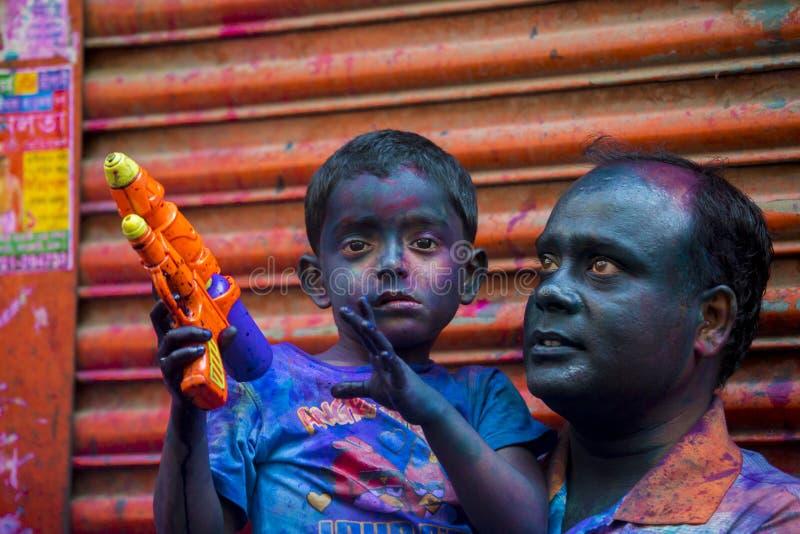 Ein Vater und ein Kinderfroher Moment des holi das Festival von Farben in Shakhari-Bazar, Dhaka, Bangladesch stockfotografie