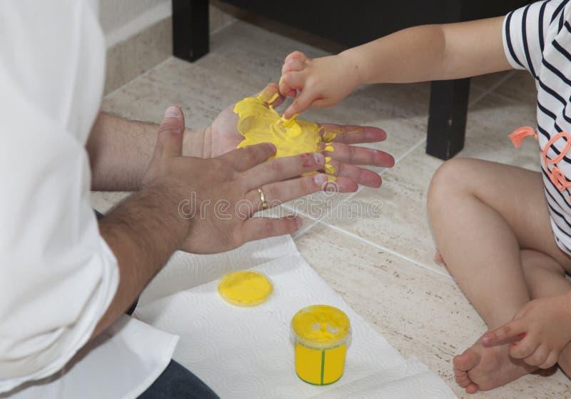 Ein Vater und seine Tochter, die mit gelber Farbe spielen lizenzfreie stockfotos