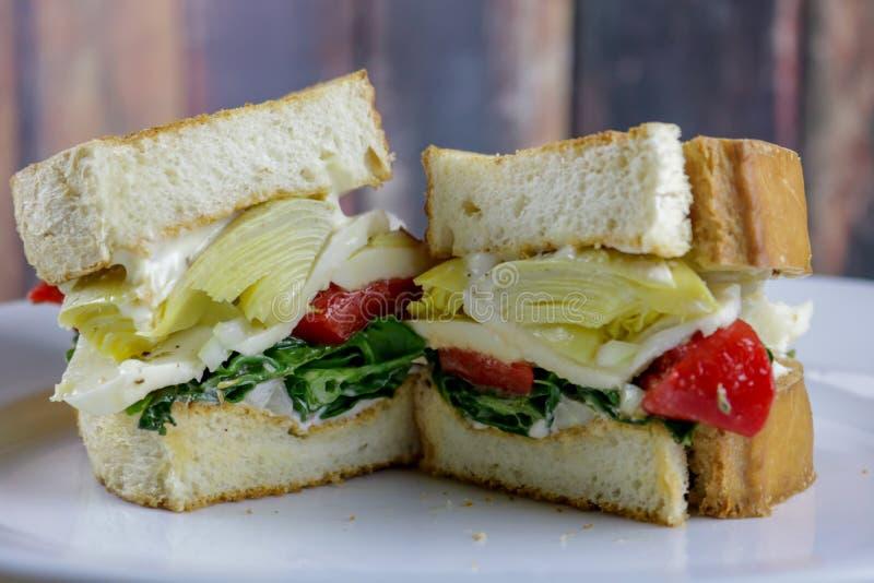 Ein Veggie-Sandwich mit marinierten roten Pfeffern, Spinat und Artischocke stockbilder
