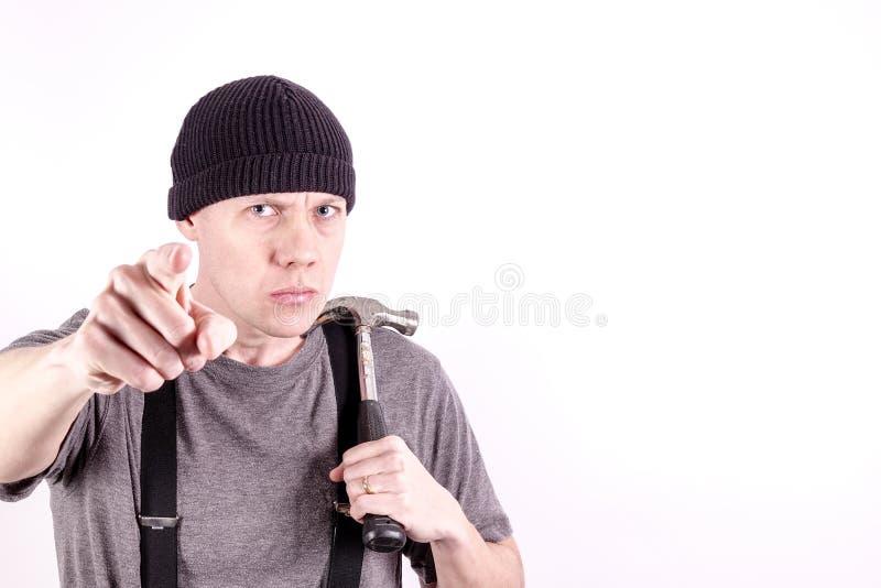 Ein verärgerter Tischler mit einem Hammer, seinen Finger zeigend stockbild