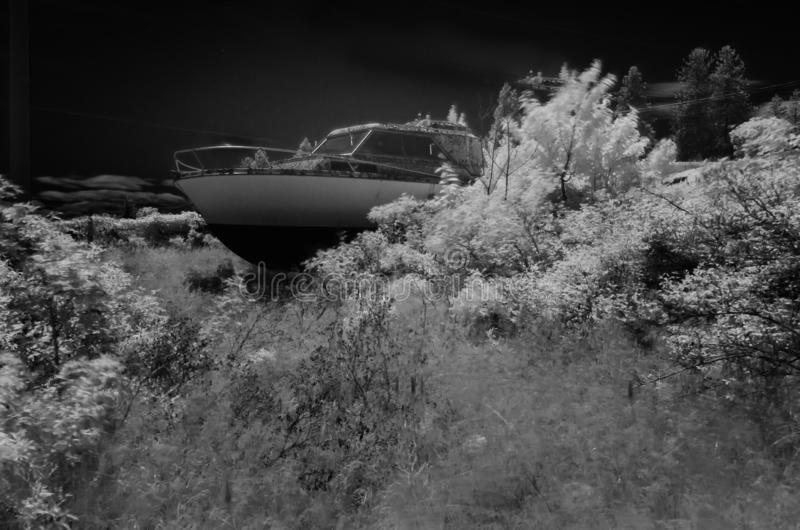Ein verlassenes verschlossenes Kajütboot des Landes auf einem überwucherten Gebiet, das in Infrarotschwarzweiss geschossen wird,  stockfotos