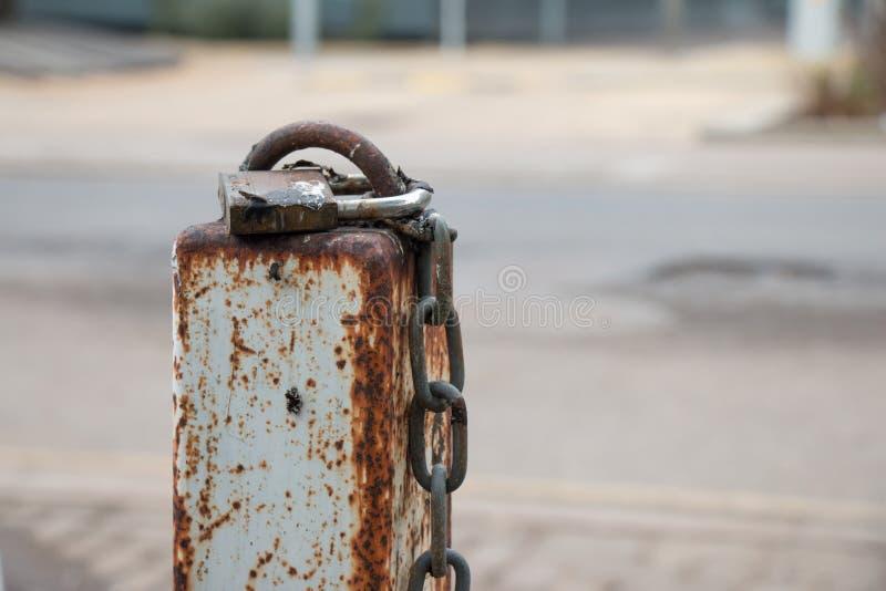 Ein Verschluss und eine Kette auf Rusty Pole stockfotografie