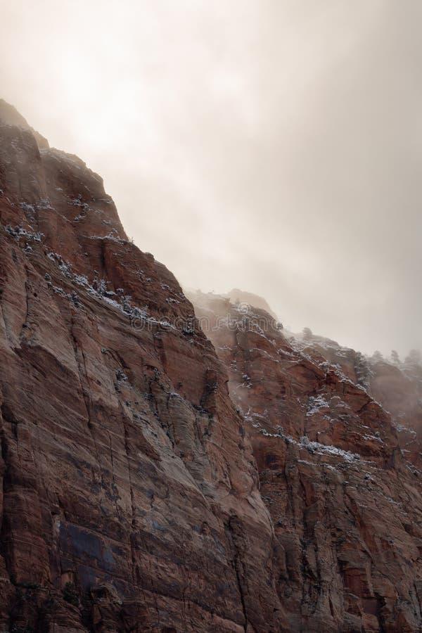 Ein vertikales Bild von den Wintersturmwolken, die über dem Schnee treiben, schnürte sich hochragende Klippen des roten Sandstein lizenzfreies stockfoto
