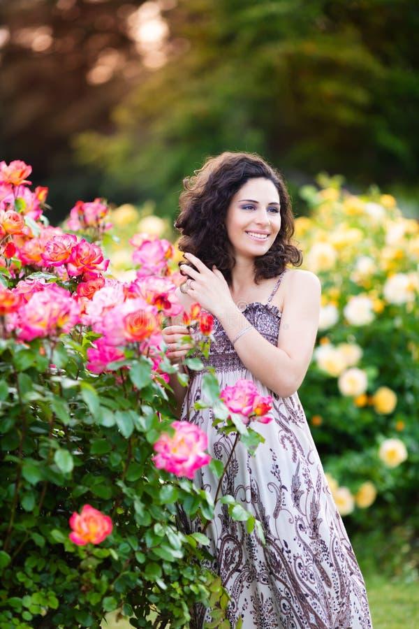 Ein vertikales Porträt der jungen kaukasischen Frau mit dem dunkelbraunen gelockten Haar nahe rosa Rosenbusch, schauend nach link lizenzfreies stockfoto