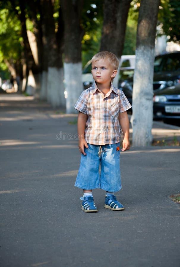 Ein Vertrag abgeschlossener Junge verloren in der Straße stockbild