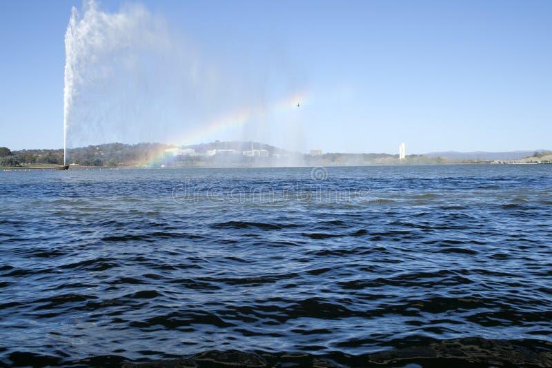 Ein Vogel fliegt durch einen Regenbogen, der durch ein Denkmal hergestellt wird, das in Canberra Wasserstrahl ist lizenzfreie stockfotos