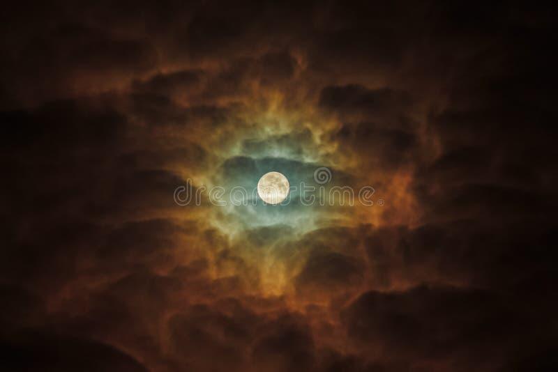 Ein Vollmond hebt ominös die dunklen Wolken hervor Sonnenblume des nächtlichen Himmels stockbild