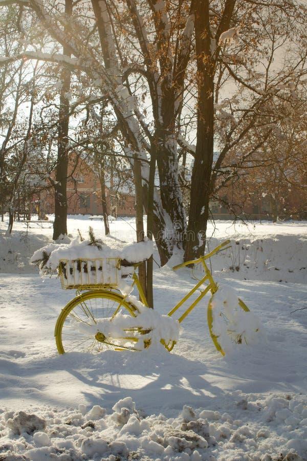 Ein vollständig gelbes Fahrrad mit einer Blume in einer Fördermaschine steht im Schnee lizenzfreies stockbild