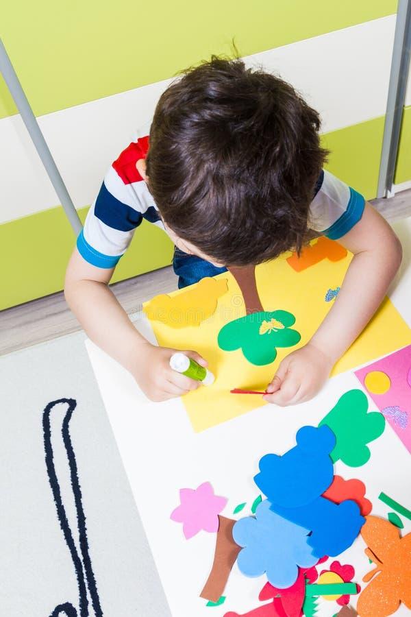 Ein Vorschuljungengebrauchskleber für die Hausarbeit empfangen vom Kindergarten stockbilder