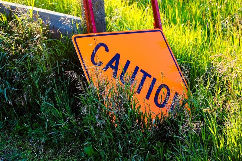 Ein Vorsichtbauzeichen, das in das Gras legt lizenzfreie stockfotografie