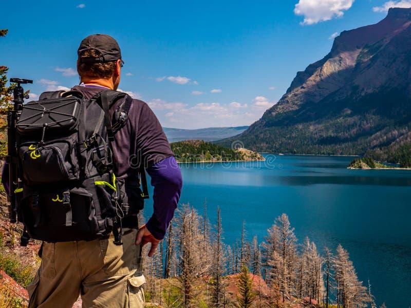 Ein Wanderer stoppt, um die Schönheit einzulassen, die St. Mary Lake ist stockbild