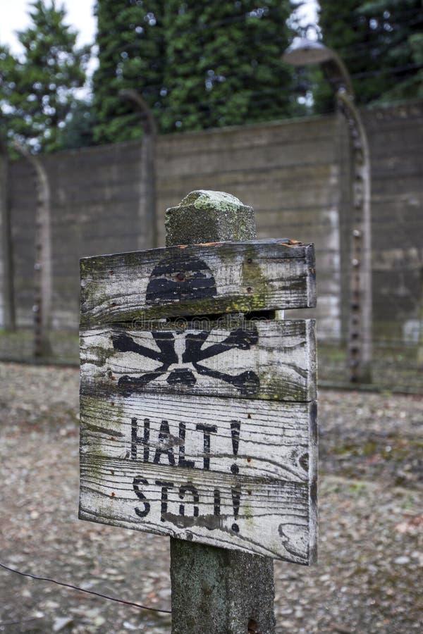 Ein Warnzeichen gelegt vor einem elektrischen Zaun des Stacheldrahts am Auschwitz--Birkenaulandesmuseum in Polen stockbild