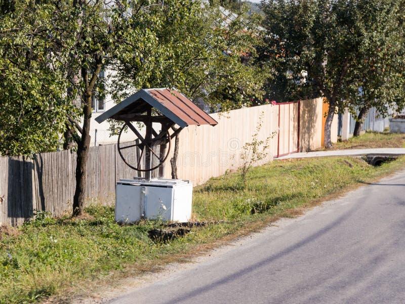 Ein Wasserbrunnen, der auf einer Dorfstraße nahe einem Zaun in Rumänien steht stockbild