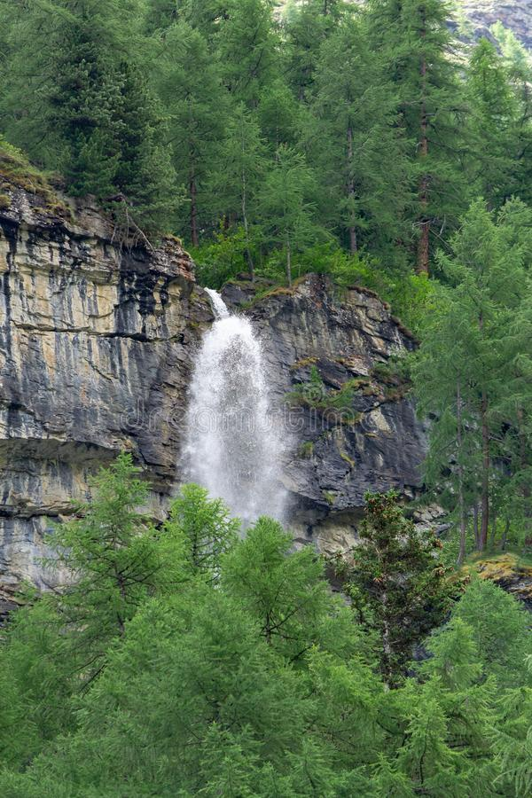Ein Wasserfall bricht durch den Berg im Wald lizenzfreie stockfotografie