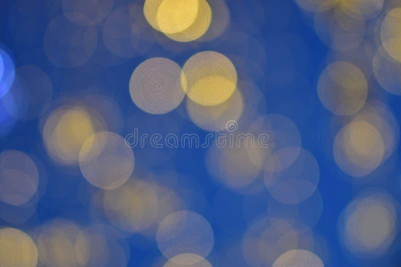 Ein Wasserfall von gelben und blauen Bällen von bokeh Nachtstädtischen Dekorationen lizenzfreies stockbild