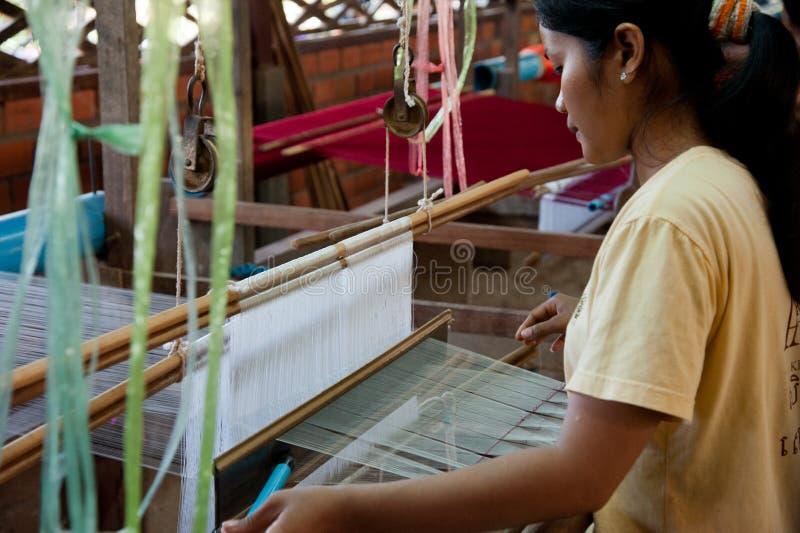 Ein Weber justiert den silk Stoff auf ihrem Webstuhl lizenzfreies stockbild