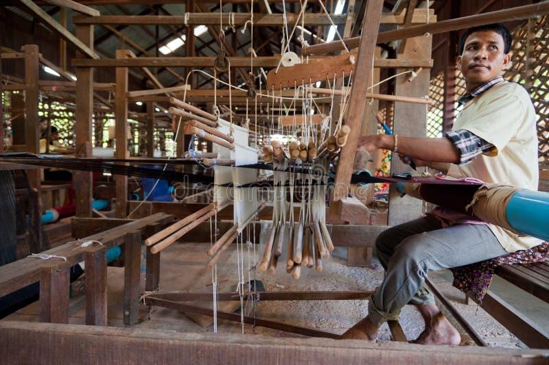 Ein Weber justiert den silk Stoff auf seinem Webstuhl stockfotos