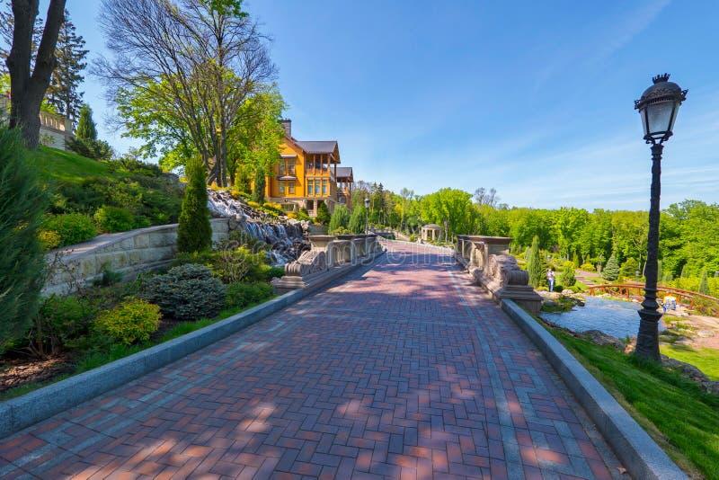 Ein Weg in einem ausgerüsteten Park nahe einem Holzhaus nahe dem Fluss mit einer Brücke lizenzfreie stockbilder