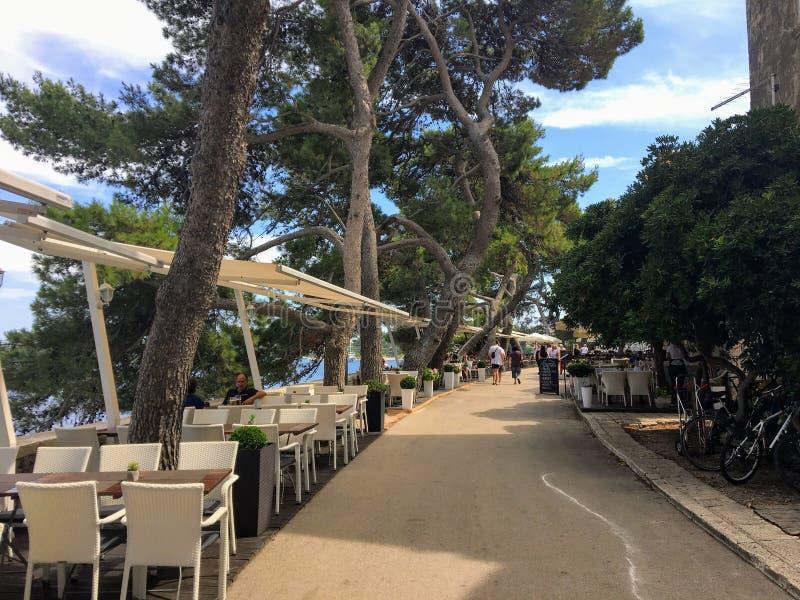 Ein Weg gesäumt von schönen Restaurants und Bäumen im Freien entlang der Altstadt von Korcula, Kroatien lizenzfreie stockfotografie