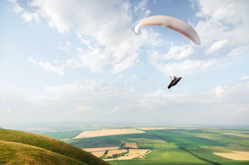 Ein weiß-orange Gleitschirm fliegt über das bergige Gelände lizenzfreies stockbild