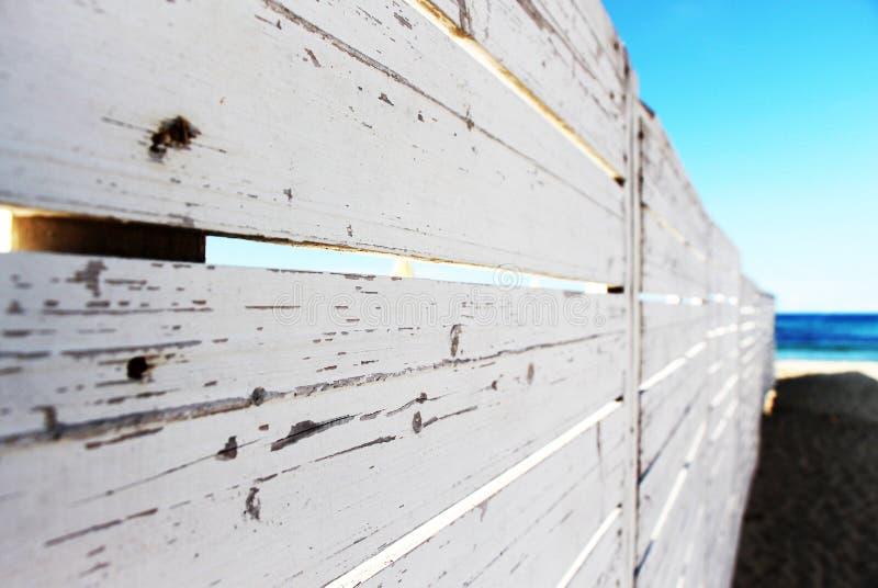 Ein weißer Bretterzaun auf dem Strand lizenzfreie stockfotografie