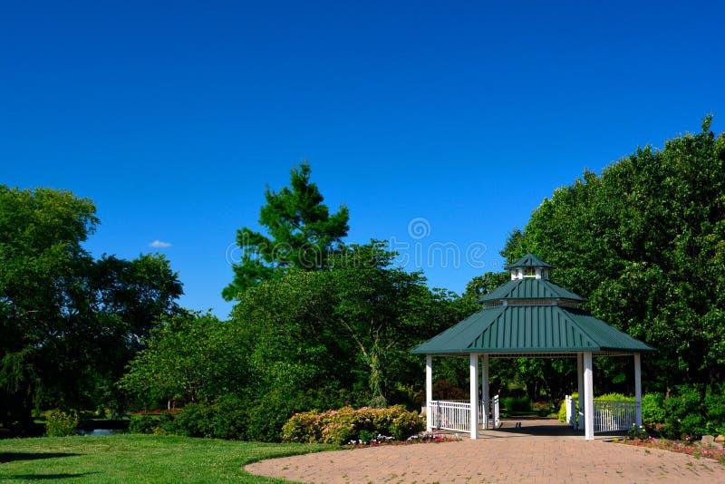 Ein weißer Gazebo mit grünem Dach-und des roten Backsteins Patio in einem Park an stockfotos